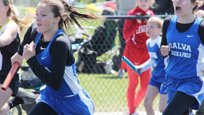 Galva's Ava Strom, right, shouts encouraging words after passing the baton to her teammate Ava Anderson in the seventh grade girls 4x100 relay at a 2019 IESA track and field sectional.