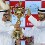 Dubai crown Prince Sheik Hamdan bin Mohammed Al Maktoum and owner of The Prince Bishop, right, and his uncle, Sheik Hamdan bin Rashid Al Maktoum holds the trophy after they won the $ 10,000,000 Dubai World Cup during the Dubai World Cup horse races at Meydan Racecourse in Dubai, United Arab Emirates, Saturday, March 28, 2015.