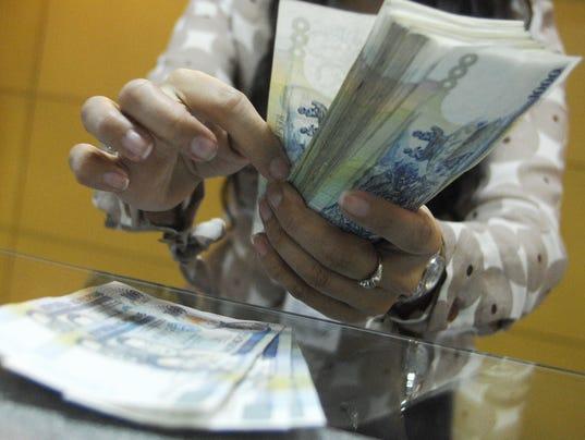 A teller shows thousand peso bills insid