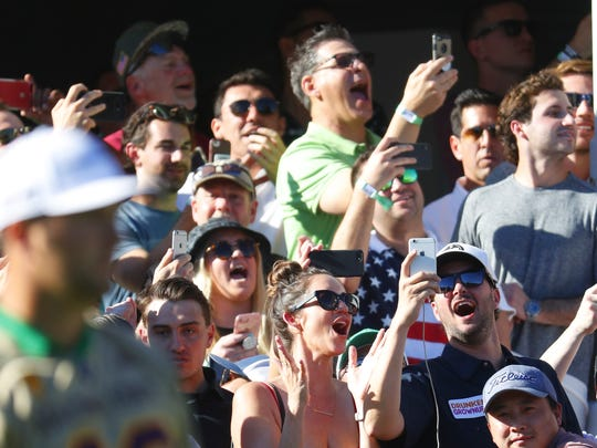 The crowd reacts as Jon Rahm, wearing an ASU Pat Tillman jersey, hits from the tee box on the 16th hole on Saturday.