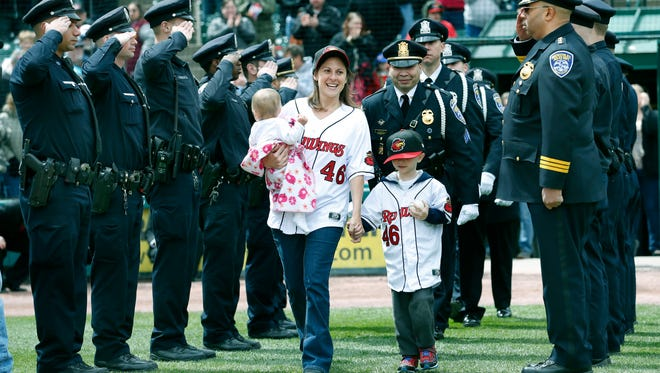 Amy Pierson walks onto the field holding her daughter Charity and son Christian as members of the Rochester Police Department salute to honor Amy's husband, fallen officer Daryl, before the Red Wings home opener against Buffalo at Frontier Field on April 11, 2015.