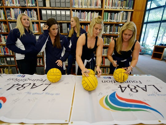 Members of the U.S. women's water polo team sign water