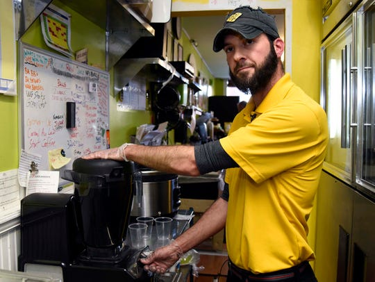Adam Armstrong, owner of Pure Juice Bar, makes charcoal