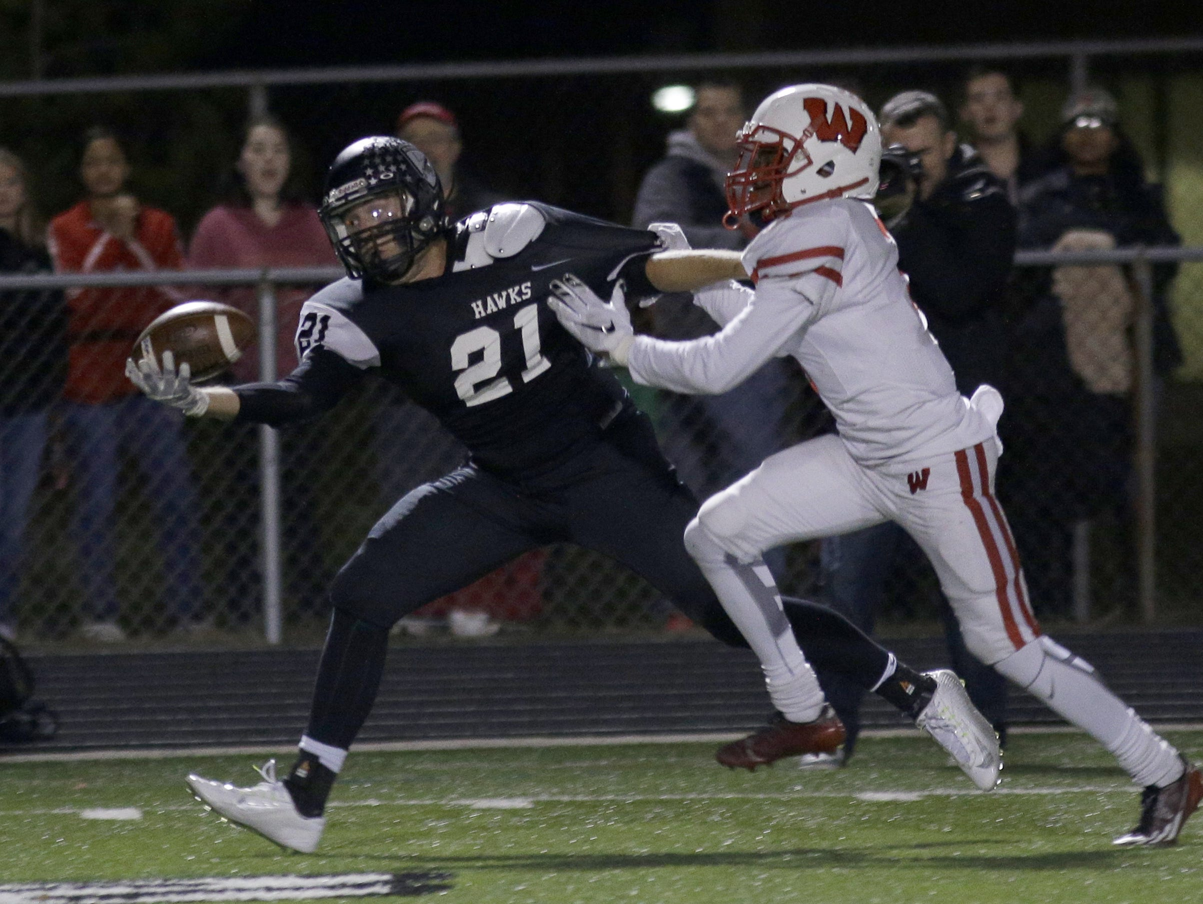 Lakota East's Austin Hatfield (21) tries to catch the ball while defended by Lakota West's Jalen Hall (3) during their football game, Friday, Oct . 30.