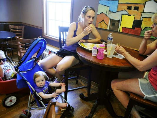 Krista McAllister of Monaghan Township eats lunch with her mother Teresa Heiges of Carroll Township, as McAllister's son Mavek, 3, and daughter Avaday, 1, chill out at Square Bean Coffee in Dillsburg. McAllister said she and her mother eat at the cafe about two or three times a week during warmer weather. Square Bean Coffee serves soups, salads, sandwiches and hot and cold beverages in Dillsburg's square.