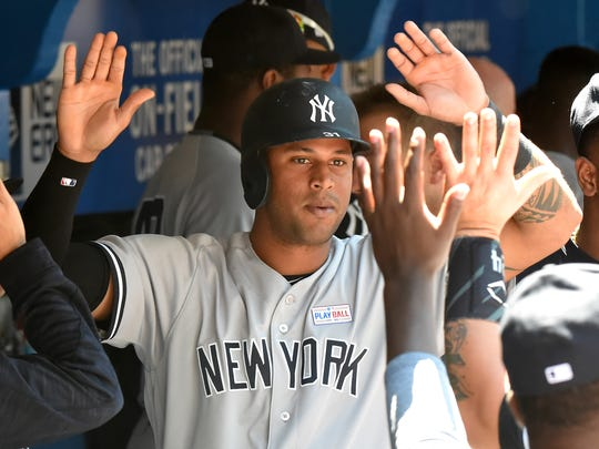 Yankees center fielder Aaron Hicks slaps hands with teammates in the dugout after scoring against Toronto Blue Jays in the third inning at Rogers Centre at Saturday, June 3, 2017.