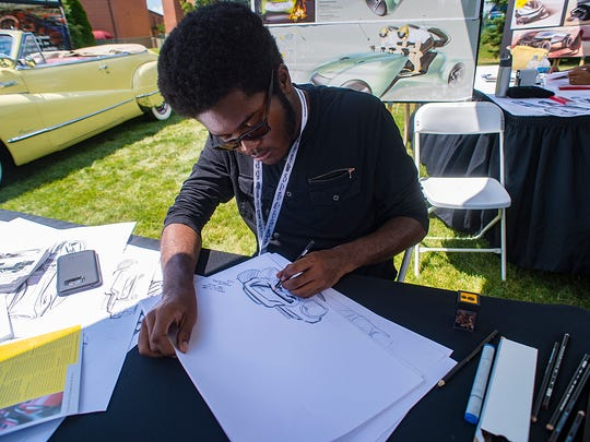 Students from Center for Creative Studies were in attendance designing cars of the future.  Christopher Hendricks of Detroit inspired by all the cars around him works on a new design.