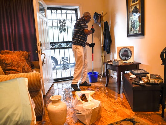 Calvin Lake cleans the floor of his flooded home on