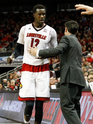 U of L head coach Rick Pitino congratulates Mangok Mathiang, #12, after playing well against Virginia Tech during their game at the KFC Yum! Center.Jan. 13, 2014