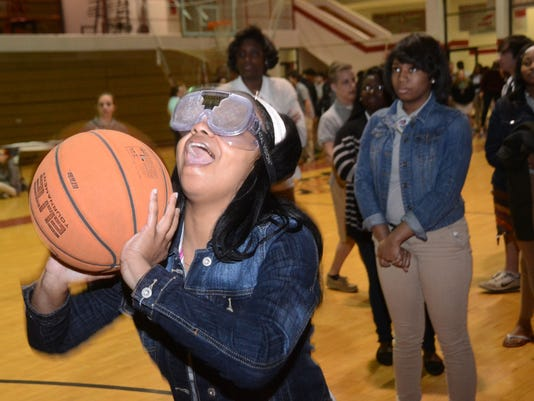 """ANI PHS Sudden Impact Pineville High School Ahmari Jacobs shoots a basket while wearing """"drunk goggles"""" during a Sudden Impact seminar held Monday, March 17, 2015. The Louisiana State Police, Rapides Regional Medical Center nurses and PHS senior Morgan Rol"""