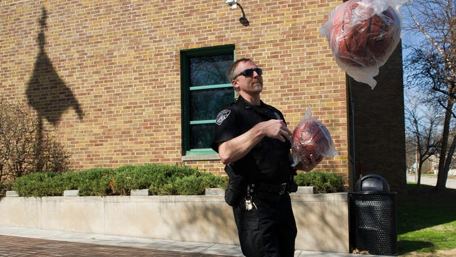 Officer Dan Deeg, Evansville Police's School Resource Officer for the Bosse District, tosses a basketball to officer Craig Pierce outside of Dexter Elementary School Thursday.