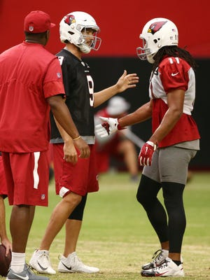 Arizona Cardinals quarterback Sam Bradford and wide receiver Larry Fitzgerald discuss the details of their pass play during training camp on Aug. 15, 2018 at University of Phoenix Stadium in Glendale, Ariz.