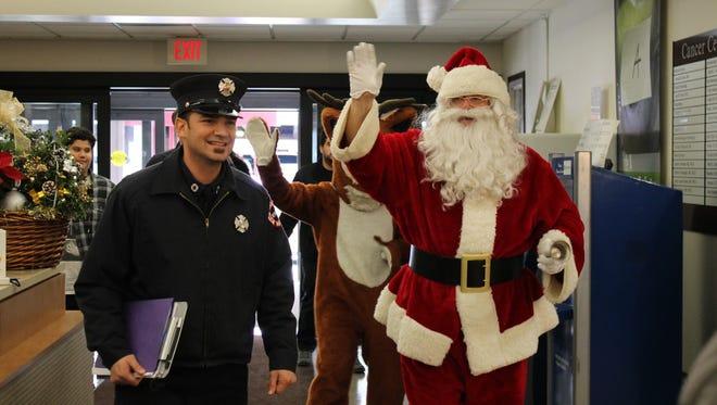 Newark Firefighter Eddie Paulo, left, and Battalion Chief Steve DeCeuster as Santa Claus walk into Clara Maass Medical Center in Belleville on Friday, Dec. 23, 2016.