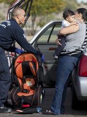 El capitán de los bomberos de Phoenix Daniel Cheatham habla con Marissa Medrano sobre como instalar el asienteo de seguridad para su hijo, Arthur Valdez de siete meses, durante el evento de The Safe Kids Coalition of Maricopa County en el Parque South Mountain Park en Phoenix el 23 de febrero de 2015.
