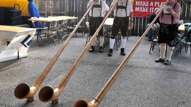 Evansville residents Charles Haas (left) and Dave Wire (center) play alpine horns along with Dan Schultz of Newburgh during the opening ceremony of a past Volksfest at Germania Maennerchor.