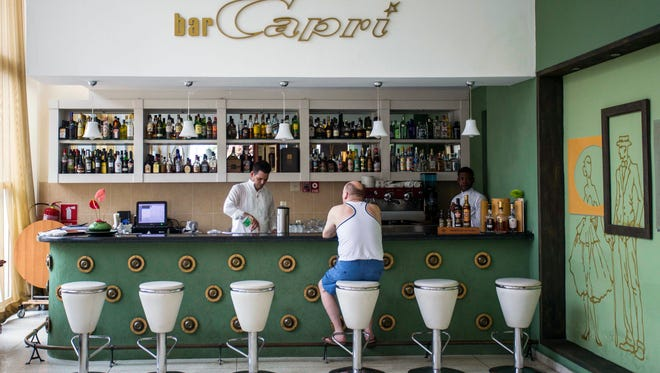 """In this Sept. 12, 2017, file photo, a customer sits at the lobby bar of the Hotel Capri in Havana, Cuba. Doctors are released the first detailed medical reports about the hearing, vision, balance and brain symptoms suffered in what the State Department has called """"health attacks"""" on U.S. diplomats in Cuba."""