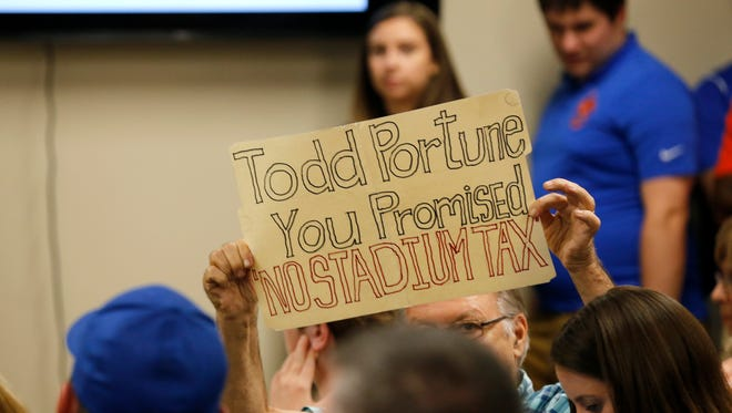 Charles Wolff, Green Township, holds up a sign as FC Cincinnati President Jeff Berding takes the podium during a County Commissioners meeting at the Hamilton County Board of Elections in Norwood, Ohio, on Tuesday, Sept. 26, 2017. The Commissioners met to discuss the future of projects in the county, including a new soccer stadium, rebuild of US Bank Arena and repairs to the Western Hills Viaduct.