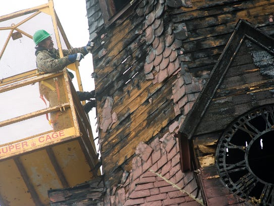 A workers carefully removes slate roofing tiles at