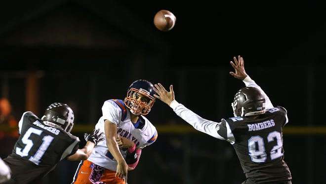 Penn Yan quarterback Will Rogers (7) stands in and delivers a pass under pressure from East Rochester/Gananda's Jack Duncan (51) and Rylee Moss (82).