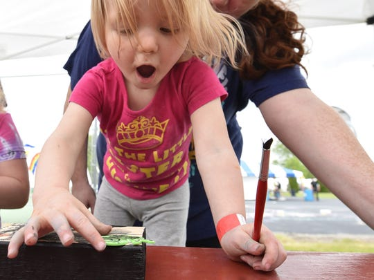 Plenty of art-related activities are held at the Sturgeon Bay Fine Art Fair. Here, Hannah Luther of Chicago seems excited about the painted, stenciled art she created on a wood block at a past fair.