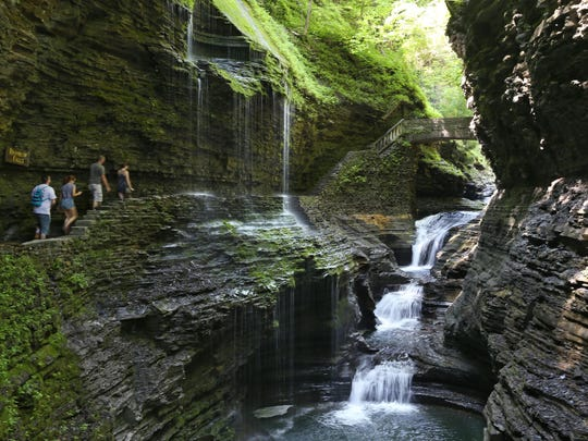 Visitors walk along the Gorge Trail and pass underneath the iconic Rainbow Falls at Watkins Glen State Park in Watkins Glen. The falls is one of two that visitors can walk underneath.