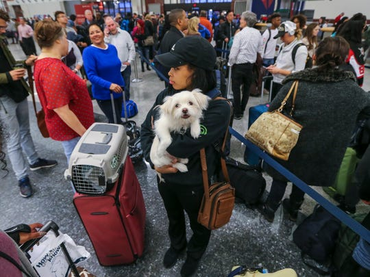 Destiny Easley and Bronx from Jacksonville, Alabama on her way to Buckeye, Arizona had to miss her flight because of the long lines at the Delta ticket counter on Monday Dec. 18, 2017 at Hartsfield-Jackson International Airport in Atlanta, the day after a massive power outage brought operations to halt. Power was restored at the airport after a massive outage Sunday afternoon that left planes and passengers stranded for hours, forced airlines to cancel more than 1,100 flights and created a logistical nightmare during the already-busy holiday travel season. (John Spink/Atlanta Journal-Constitution via AP)