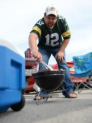Bob Schoen, iron Ridge, grills bratwurst before the