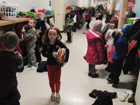 Fern Ulrich, first grader, grabs her books and heads to class to start her day at Washington Elementary school. The Oshkosh school district is holding public input sessions on changing school start times to what they were a two of years ago.