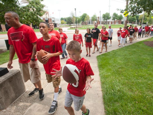 Wesley Upton and his son, Jordan, 14, of Versailles, Ky., and Owen Hillerich, 7, of Fern Creek, wait to get their footballs signed by members of the team at UofL Fan day in Cardinal Arena.  16 August 2014