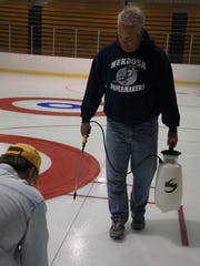 Paul Liebherr, right, and Mitch Wayne put down the lines for the curling sheets in preparation for this weekend's Marsh Madness Summer Bonspiel at the SWC Recreation Center.