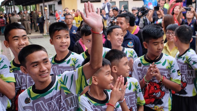 "Twelve boys and their coach from the ""Wild Boars"" soccer team arrive for a press conference for the first time since they were rescued from a cave in northern Thailand last week, July 18, 2018."