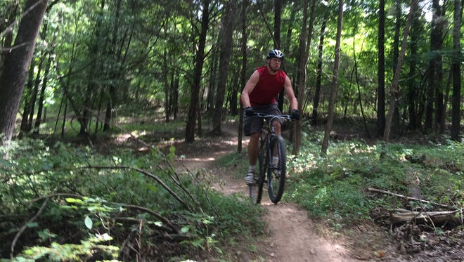 Drew Sanford rides over a bump on a trail he built at North Ford Street Mountain Bike Trail Park.