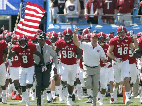 In this Sept. 2, 2017, file photo, North Carolina State head coach Dave Doeren, second from right, leads his team onto the field for an NCAA college football game against South Carolina in Charlotte, N.C.