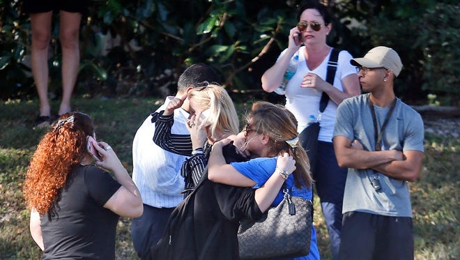 Family members wait for news of students after a school shooting.