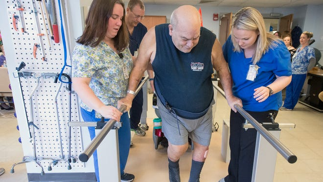 """Robert Brenner, center, is helped by Sara Soler, left, and Tasha Barcikowskiat at Pleasant Acres Nursing Home's new rehab gym. Brenner, a stoke patient says, """"If it wasn't for here, no telling where I'd be."""" Brenner uses the gym three to five times a week for therapy."""