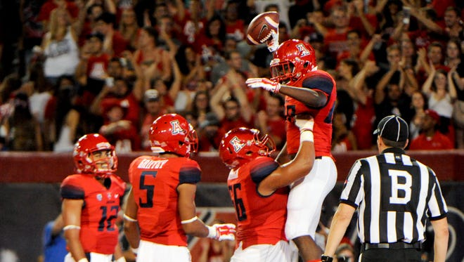 Arizona Wildcats running back Nick Wilson (28) is lifted up by offensive linesman Steven Gurrola (56) after scoring a touchdown during the second quarter against the Nevada Wolf Pack on Sept. 13, 2014, at Arizona Stadium.