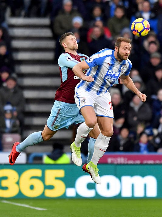 Burnley's Johann Berg Gudmundsson, left, and Huddersfield Town's Laurent Depoitre battle for the ball during the English Premier League soccer match at John Smith's Stadium, Huddersfield, England, Saturday Dec. 30, 2017. (Anthony Devlin/PA via AP)