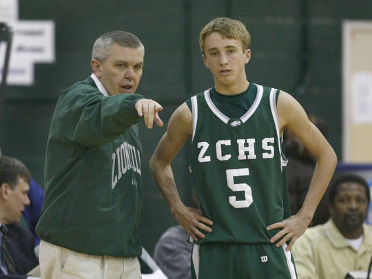 FILE – Zionsville coach Shaun Busick talks to Jay Townsend, 5, during a break in game action, as Zionsville defeated Attucks, Dec. 13, 2008.