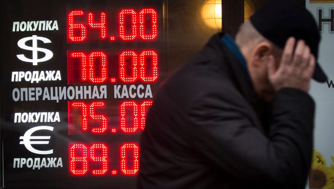 Signs advertising currencies sit next to an exchange office in Moscow on Dec. 16.