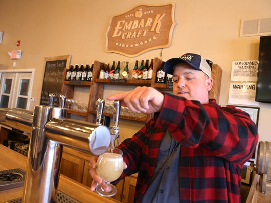 Jacob Lagoner pours a glass of American Hopped Cider in the tasting room at Embark Craft Ciderworks.