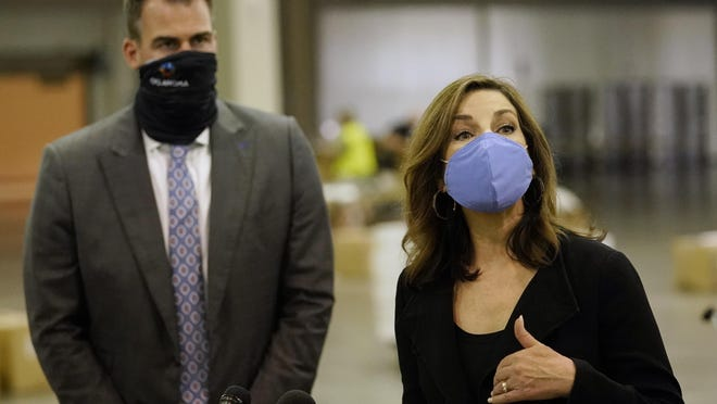 Oklahoma State Superintendent of Public Instruction Joy Hofmeister, right, answers a question at the Central Oklahoma PPE distribution warehouse where supplies for schools are being distributed Tuesday, Aug. 18, 2020, in Oklahoma City. Listening at left is Oklahoma Gov. Kevin Stitt.
