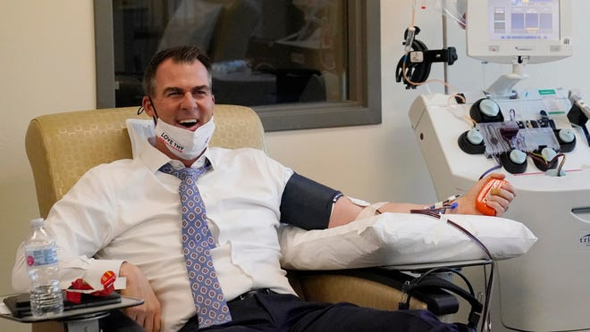 Oklahoma Gov. Kevin Stitt talks with the media as he donates convalescent plasma at the Oklahoma Blood Institute in Oklahoma City on Tuesday. It was Stitt's second time donating plasma since he tested positive for the coronavirus in July.