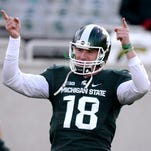 Quarterback Connor Cook salutes the student section as they cheer for him as the team warms up before the game with Penn State Saturday, November 28, 2015, at Spartan Stadium in East Lansing.