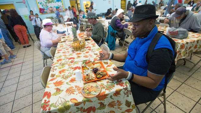 Jeromy  O. Anderson, sits down to enjoy a Thanksgiving Day meal at el Caldito Soup Kitchen, Thursday Nov. 23, 2017.