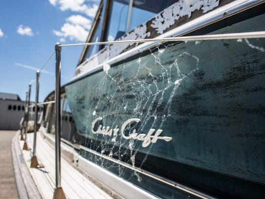 A spider web is seen on an abandoned Chris-Craft boat