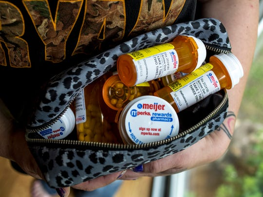 Aimee Dort shows a cosmetic bag she uses to hold her pill bottles Thursday, June 23, 2016 at her Kimball Township home.