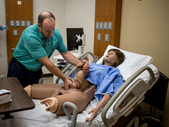 Simulation Lab Technician Sean Murphy places an infant into a birthing simulator while organizing equipment Tuesday, August 23, 2016 in the Health Sciences Simulation Center in the A.J. Theisen Building at St. Clair County Community College in Port Huron.