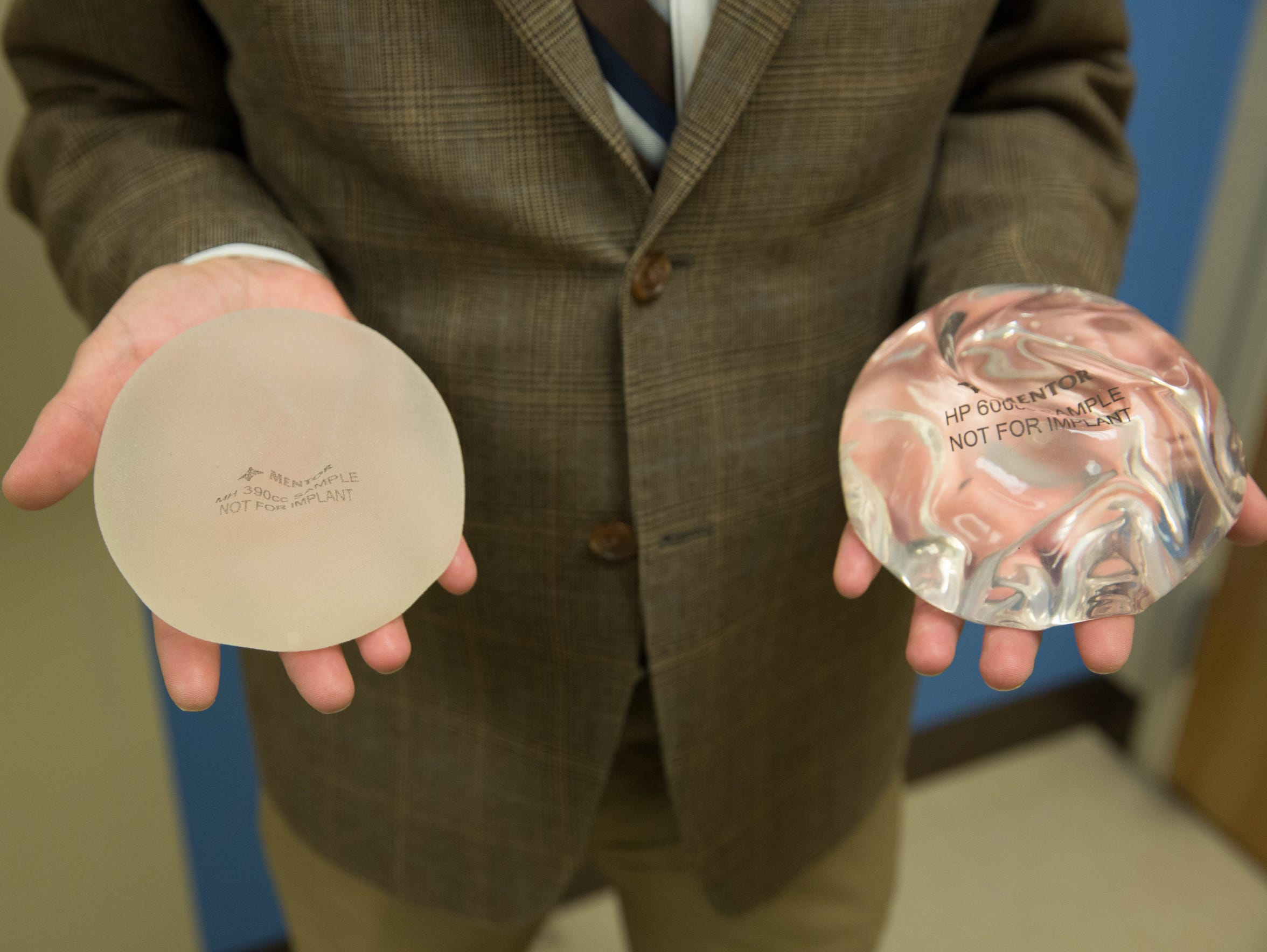 Dr. Paul Phillips holds two different types of breast