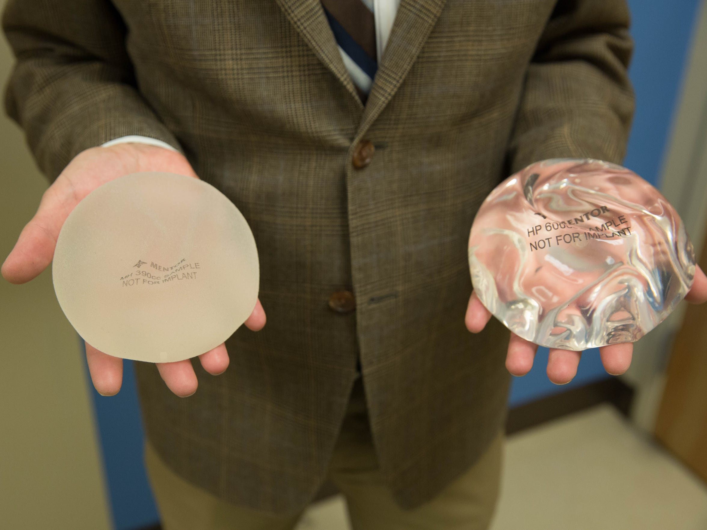 Dr. Paul Phillips holds two different types of breast implants, one for reconstructive surgery, left, and one for cosmetic surgery, right.