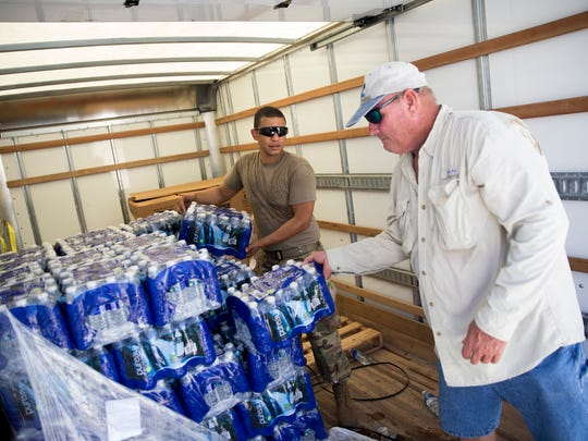 Electronic gadgets take a backseat when basics, such as food and water, become scarce. Here, supplies, courtesy of the American Red Cross, are distributed Tuesday in Everglades City.